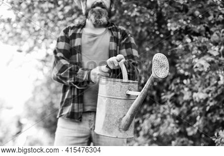 Man Using A Big Watering Can For Planting. Pour The Water. Man With Watering Can. Gardening And Wate