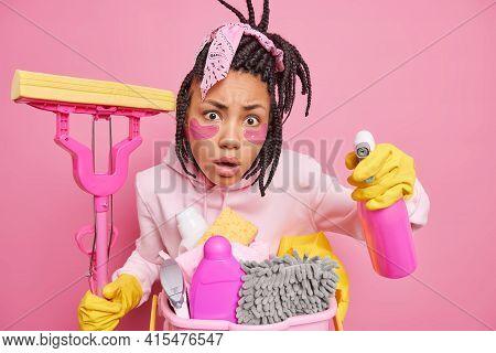 Housekeeping Duties Concept. Surprised Dark Skinned Woman With Dreadlocks Applies Collagen Pads Unde