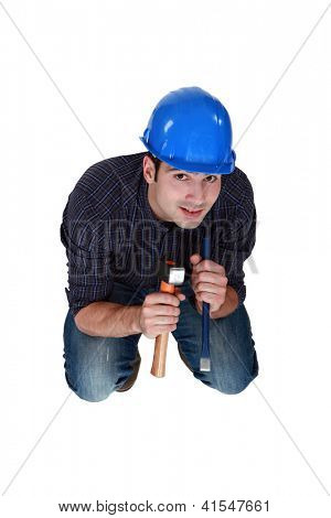 Tradesman holding a hammer and chisel