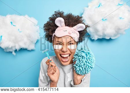 Emotional Curly Afro American Woman Screams Loudly Wears Sleepmask Holds Razor And Sponge Going To T
