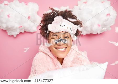 Beautiful African American Woman Smiles Broadly Bites Lips Applies White Strip Nose Mask For Cleansi