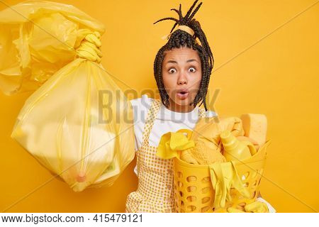 Cleaning Service And Chores Concept. Astonished Dark Skinned Woman With Combed Dreadlocks Dressed In