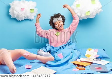 Relaxed Satisfied Afro American Student Wakes Up In Morning Ready For Productive Day Stretches In Be
