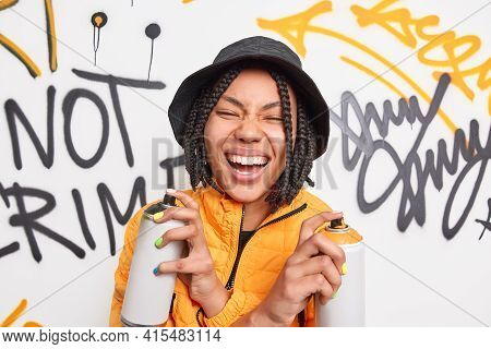 Positive Female Teenager Holds Aerosol Sprays Crosses Hands Laughs Happily Wears Fashionable Clothes