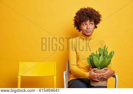 Horizontal Shot Of Pretty African American Woman Being Deep In Thoughts Holds Potted Cactus Concentr