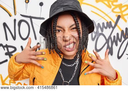 Rock Style And Urban Lifestyle Concept. Cheeky Dark Skinned Woman Smirks Face Raises Hands Enjoys Ra