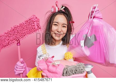 Happy Smiling Asian Housekeeper Holds Polythene Litter Bag And Mop Satisfied With Results Of Housewo