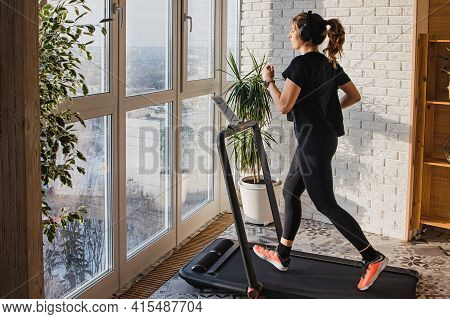 Woman Jogging On The Modern Compact Treadmill At Home