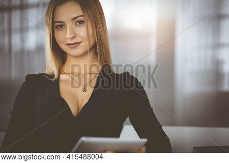 Successful Young Businesswoman Is Using A Computer Tablet, While Working In A Sunny Cabinet Of Her F