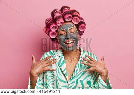 Studio Shot Of Satisfied Afro American Lady Smiles Broadly Enjoys Skin Care Treatments Applies Nouri