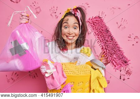 Housekeeping And Maintenance Concept. Positive Young Asian Woman Picks Litter In Polythene Bag Holds
