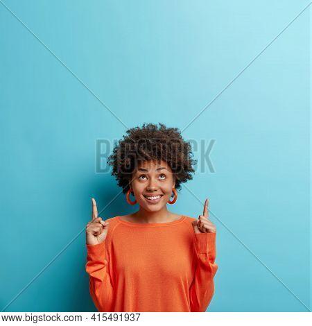 I Want It. Positive Dark Skinned Female Model Wears Casual Orange Jumper Points Index Fingers Above