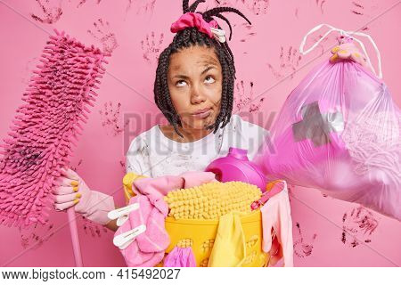 Tired Thoughtful Housewife Poses With Rubbish Bag And Mop Stands Dirty After Doing Housework Cleans