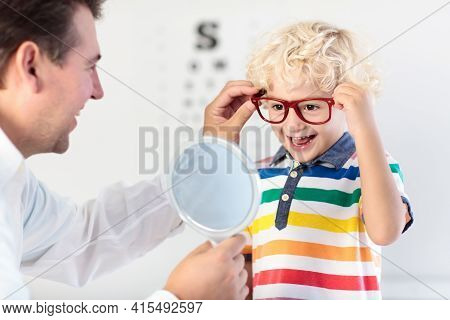 Child At Eye Sight Test. Little Kid Selecting Glasses At Optician Store. Eyesight Measurement For Sc