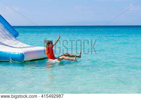 Kids Jumping On Trampoline On Tropical Sea Beach. Children Jump On Inflatable Water Slide. Aqua Amus
