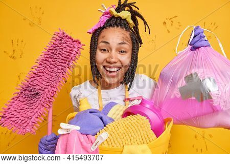 Positive Dark Skinned Woman Stands Dirty After Overall Cleaning Does Housework Holds Garbage Bag And