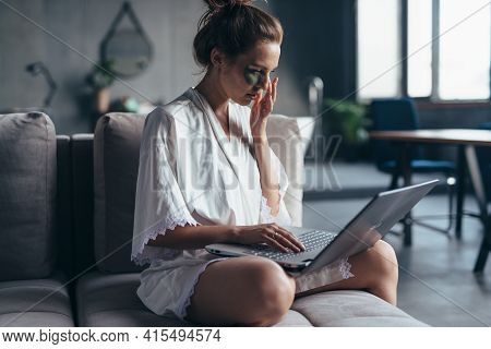 Woman Sits At Home On The Couch In A Nightgown With A Laptop