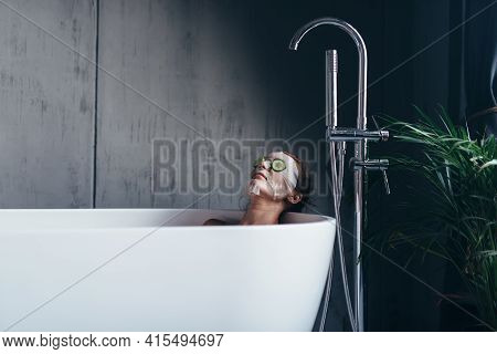 Young Woman Lies In The Bathtub With A Mask And Cucumbers On Her Face