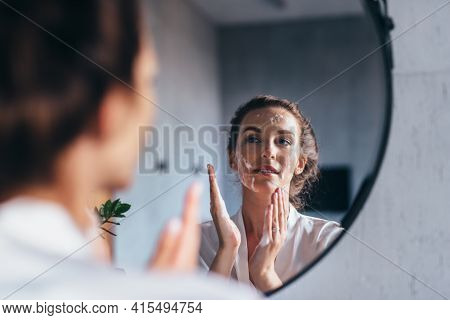 Woman Washes In Front Of The Mirror, Applying Foam To Her Face