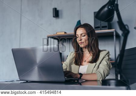 Woman Works In Her Office Sitting At Her Desk With A Laptop