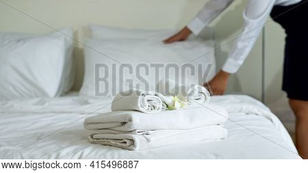 Closeup White Towel With White Flower On Bed. Young Hotel Maid Making The Bed In The Background.