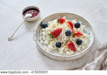 Cottage Cheese With Blueberries And Strawberries In Plate On Light Background. Nearby Raspberry Jam