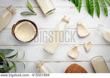 Vegan Non Dairy Coconut Milk In Bottles On White Wooden Background. Lactose Free Milk Substitute. To
