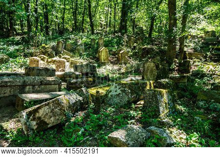Ancient Cemetery Overgrown By Forest. Many Gravestones Are Covered With Moss. Writings On Them Are E