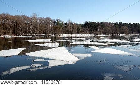 Natural Landscape With Ice Floes Adrift On The Spring River And Forest Trees On Opposite Bank Under
