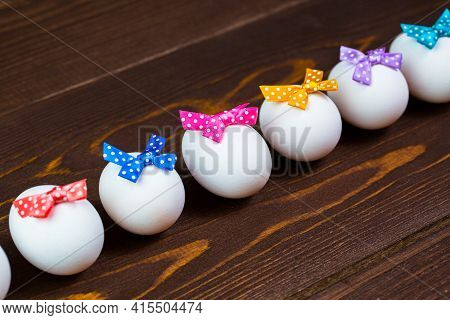 Line Of Easter Eggs With Colorful Bows Are On The Wooden Background.