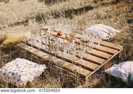 Set Of Elegant Glassware Placed On Plank Wooden Table With Floral Arrangement On Grassy Meadow Durin