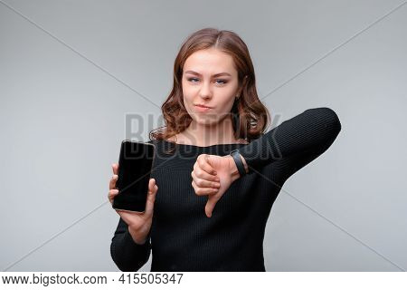 Portrait Of A Nice Young Brunette Woman Holding Smartphone And Showing Thumb Down, Girl Dont Recomme