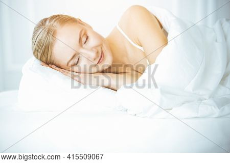 Happy Woman Sleeping In Bedroom Comfortably And Blissfully. Waking Up In Sunny Morning