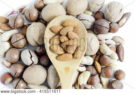 Nuts Almonds In A Wooden Spoon On The Background Of A Scattering Of Different Nuts Assorted Nuts