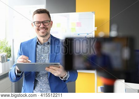 Smiling Businessman Holding Clipboard And Conducting Online Business Development Courses