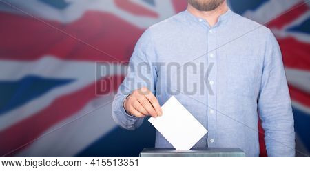 Election in UK. Hand of voter putting vote in the ballot box. Waved United Kingdom flag on background.
