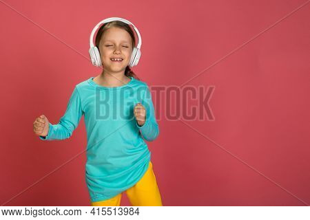 Little Beautiful Baby Girl Pink Background Bright Clothes Yellow Pants Turquoise Blue Shirt Wearing White Headphones Listening To Music And Dance