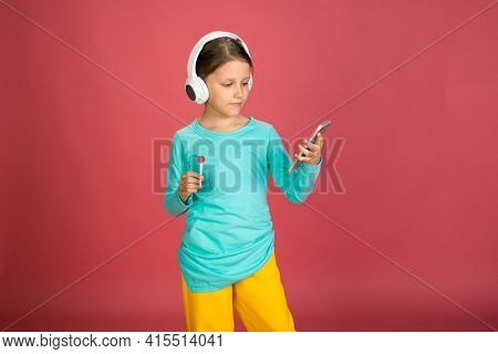 Little Beautiful Baby Girl Pink Background Bright Clothes Yellow Pants Turquoise Blue Shirt Wearing White Headphones Listening To Music With Smartphone In Hand With Lollipop