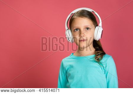 Little Beautiful Baby Girl Pink Background Bright Clothes Yellow Pants Turquoise Blue Shirt Wearing White Headphones Listening To Music