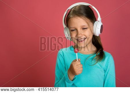 Little Beautiful Baby Girl Pink Background Bright Clothes Yellow Pants Turquoise Blue Shirt Wearing White Headphones Listening To Music With Lollipop