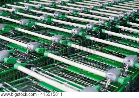 Many Empty Green Shopping Carts In Row. Row Of Parked Trolleys In Supermarket.