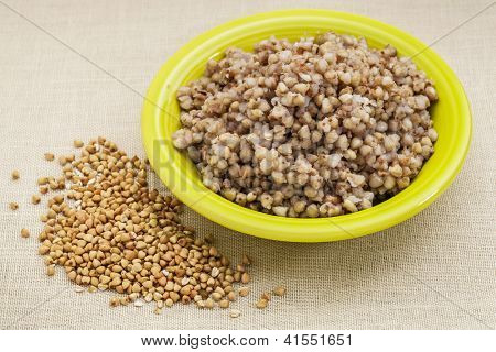 bowl of cooked buckwheat kasha with roasted grain sprayed over canvas background