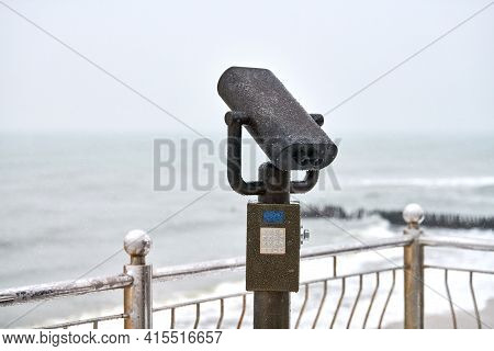Coin-operated Binocular Viewer Next To Waterside Promenade. Landscape With Beautiful Cloudy Sky And