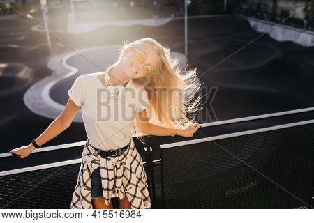 Joyful Young Woman Spending Sunny Day In Skate Park. Outdoor Portrait Of Fair-haired Girl In White H