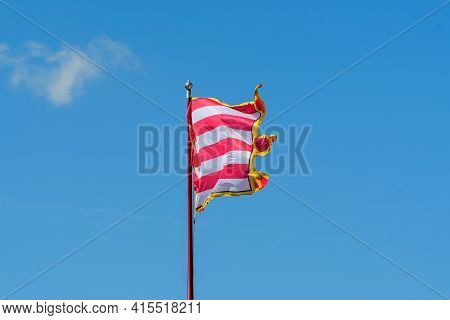 Vivid Colorful Flag Blowing In The Wind In Direct Sunlight Towards Clear Blue Sky In A Sunny Day Nea