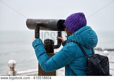 Woman In Green Down Jacket Looking At Sea Through Coin-operated Binocular Viewer In Winter. Tourism