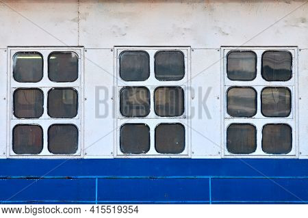 Three Cabin Windows And Portholes On Outboard Side Of Ship. Close Up Of Hull Of Vintage Ocean Liner.