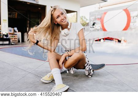 Pretty Woman In Yellow Shoes Sitting On Longboard With Legs Crossed. Outdoor Photo Of Stunning Tanne