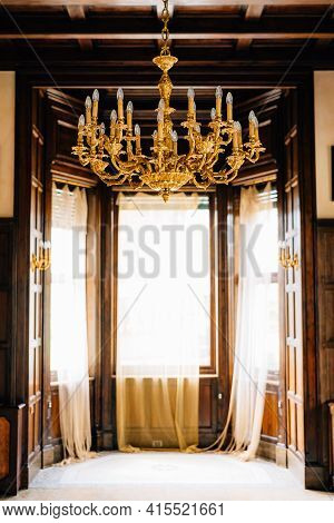 The Interior Of An Old Italian Villa, Large Windows And A Large Golden Chandelier With Candles.