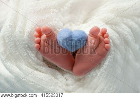 Newborn Baby's Bare Heels Hold A Blue Heart On A White Background. Bare Heels Of A Newborn In A Whit